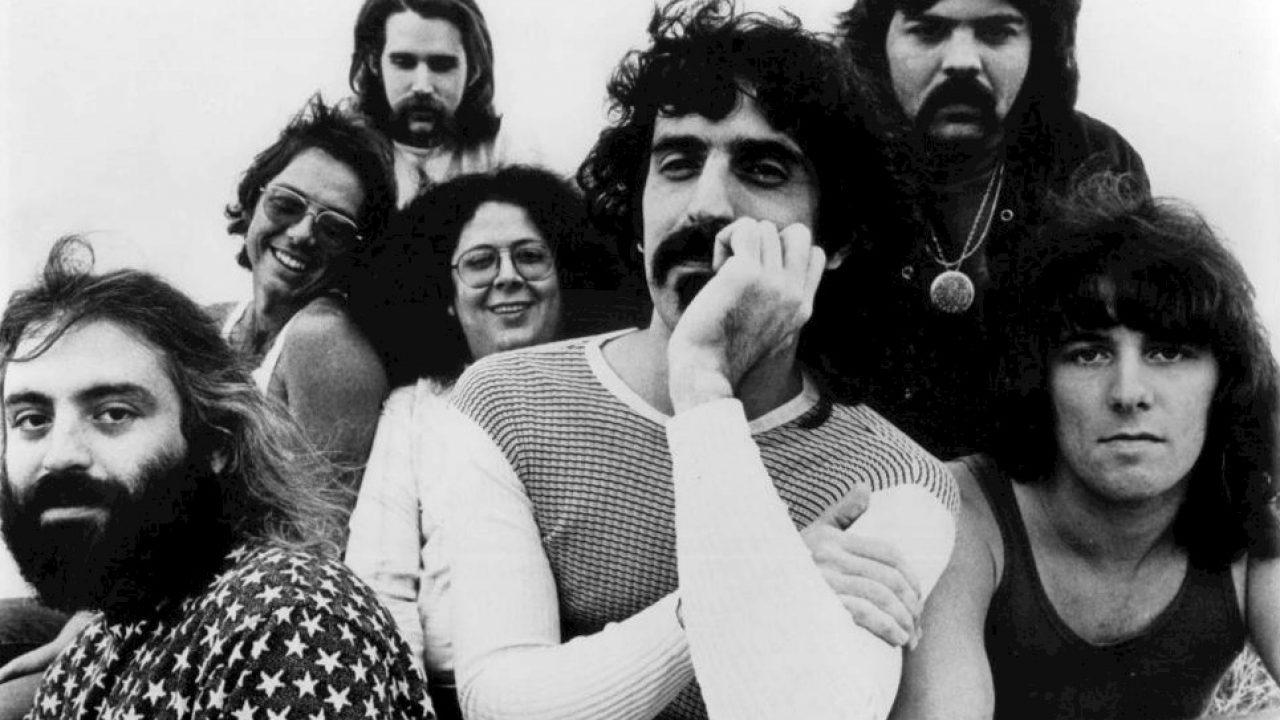 Frank Zappa néz felénk a WC-ből, bokáig letolt nadrággal