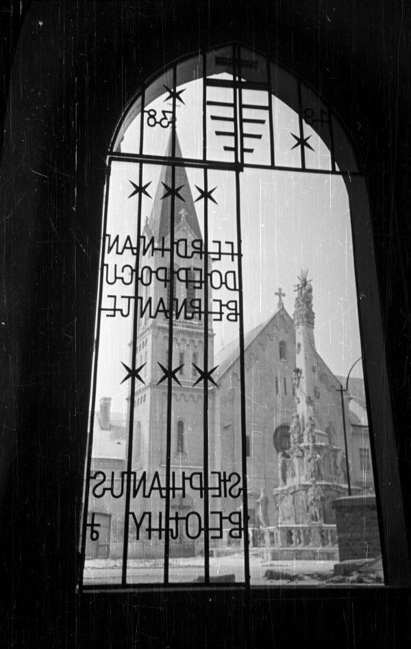 Szentháromság-szobor mögött a Szent István ferences templom - Fortepan, CC BY-SA