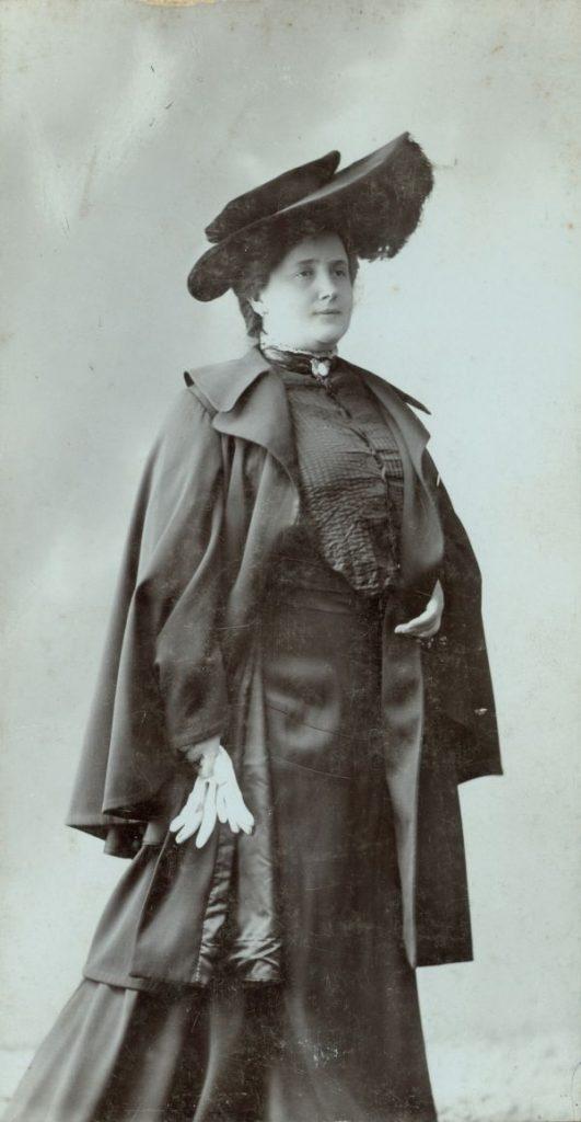 Lukács Júlia sötét utazóruhában, kalapban, kesztyűvel - Déri Múzeum, CC BY