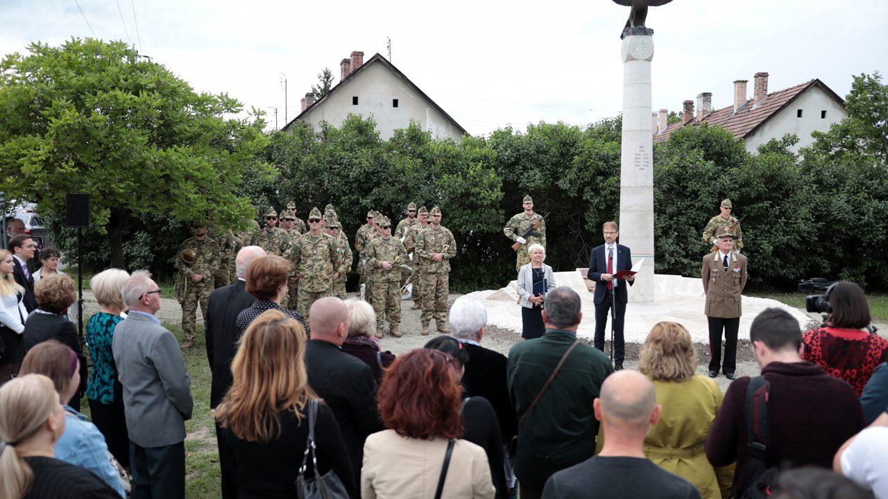 Az emlékmű egy gyűrött katonakabát, a rajta lévő rohamsisakból töltények, kitüntetések ömlenek ki